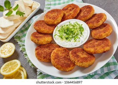 delicious crispy rice cutlets with finely chopped greens on a white platter with yogurt sauce in center and paneer cheese on a rectangular plate, quick and easy recipe, view from above, close-up