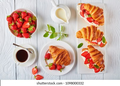 delicious croissant sandwiches with fresh ripe strawberries and cream cheese on a platter. a cup of coffee, jug of fresh cream and bowl with strawberries on a wooden table, view from above, close-up