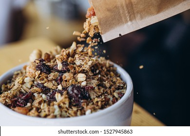 a delicious and crunchy oatmeal granola with honey, nuts, dried fruits and grains is poured out of the praml package into a plate. Dynamic healthy food photography
