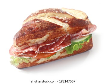 Delicious crusty brown lye bread roll sandwich, a traditional German and Bavarian bread glazed with lye, with spicy salami sausage, lettuce, cucumber and tomato on white