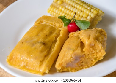 Delicious Cuban tamales stuffed with pork next to a boiled corn on the side and a wild red cherry as decoration. Tamales are one of Cuba's most enjoyed traditional dishes.