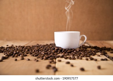 A delicious cup of coffee on a table with roasted coffee beans