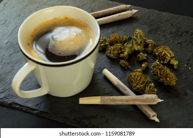 Delicious cup of coffee, a pile of high quality marijuana buds with some cigars of weed ready to smoke. Top view with background of black stone.