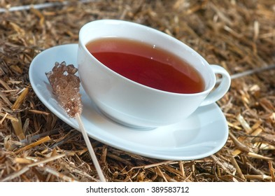 delicious cup of tea on straw background