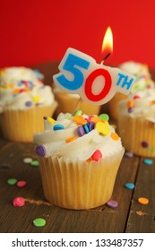 Delicious cupcake with 50th candle on top and 49 other cakes in background