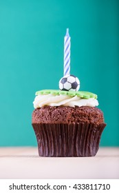 Delicious cupcake with ball icon on it and candle on wooden desk and green background