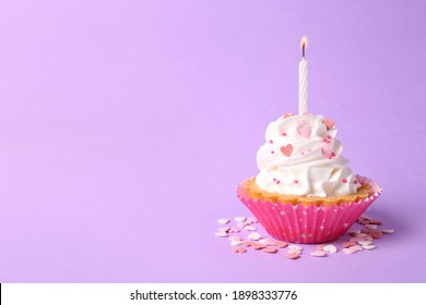Delicious cupcake with candle on violet background. Space for text