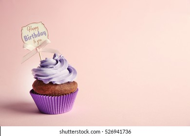 Delicious cupcake with greeting card on color background. Text HAPPY BIRTHDAY TO YOU on card.