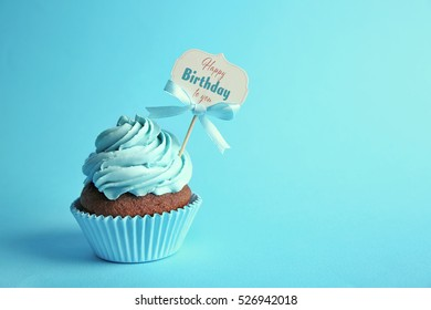 Delicious cupcake with greeting card on blue background. Text HAPPY BIRTHDAY TO YOU on card.