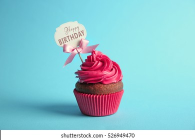 delicious cupcake with greeting card on blue background text happy birthday on card