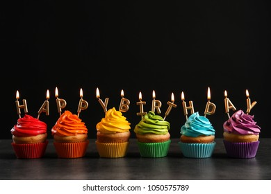 Delicious cupcakes with Happy Birthday candles on table against black background