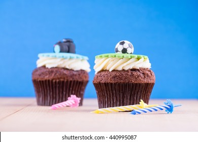 Delicious cupcakes with icons of ball and camera on it on wooden desk and blue background