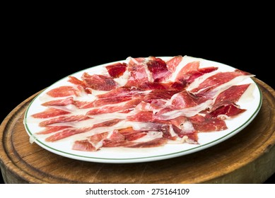 Delicious cured ham isolated on black background