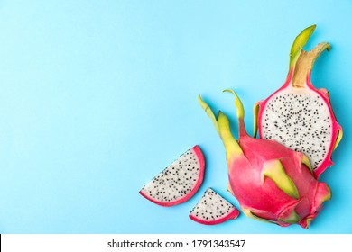 Delicious cut dragon fruit (pitahaya) on light blue background, flat lay. Space for text