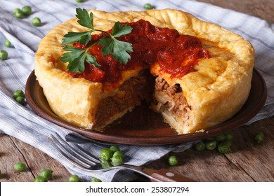 delicious cut meat pie on a plate close-up. horizontal, rustic style
