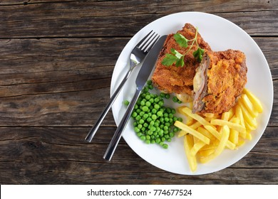 delicious Cutlet Cordon Blue with French fries, green peas and parsley on plate on old dark wooden table, authentic recipe, horizontal view from above