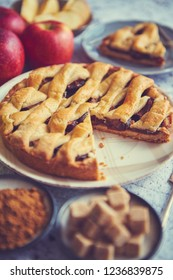 Delicious cutted apple pie cake with a fresh red and green apples fruits, brown and powder sugar. Placed on rusty scratched stone table.
