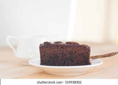 Delicious dark chocolate cake on white plate with coffee in relaxing time. Copy space.