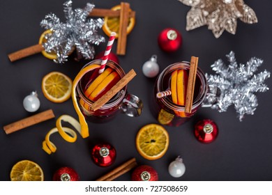 Delicious dark cinnamon tea with orange slices and peels over striped red and white background red mulled wine hot punch