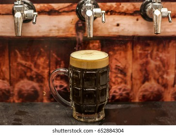 Delicious dark craft beer filled into a pint glass on wooden table