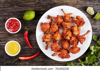 delicious deep fried battered crispy chicken winglets  with exposed bones on a white plate on dark wooden table with mustard and tomato sauce in gravy boats at background,, horizontal view from above