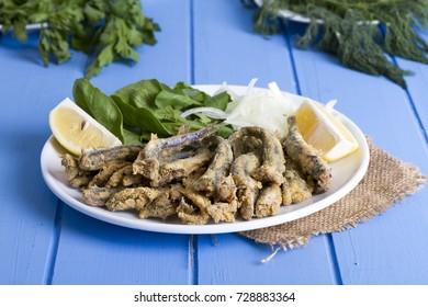 Delicious Deep Fried European Anchovy Fish serving on white round plate with sliced onion, green arugula salad, parsley, tomato and juicy lemon on rustic blue wooden table background. Copy space area.
