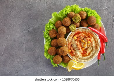 delicious deep fried falafel balls with hummus in a bowl, chili peppers and lettuce leaves on plate on concrete background, horizontal view from above, close-up