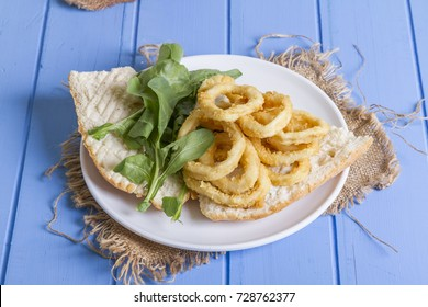 Delicious Deep Fried Rings Sandwich serving with white circle plate, half of bread, sliced onion and green arugula salad on rustic blue wood background. Squid is eaten in many cuisines. Top View.