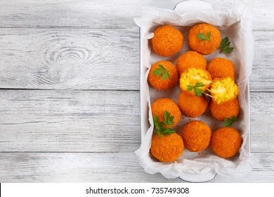 delicious deep fried sicilian arancini - saffron rice balls stuffed with cheese in baking dish on old wooden table, horizontal view from above