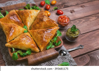 Delicious deep fried south Indian Samosa pies with meat, lettuce, mint chutney and tomato sauce on a wooden background in rustic style, empty place for text