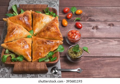 Delicious deep fried south Indian Samosa pies with meat, lettuce, mint chutney and tomato sauce on a wooden background in rustic style, top view, empty place for text