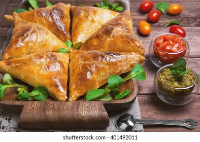 Delicious deep fried south Indian Samosa pies with meat, lettuce, mint chutney and tomato sauce on a wooden background in rustic style