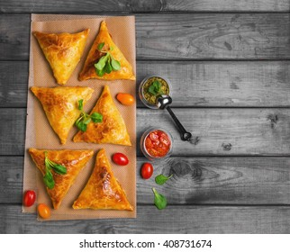 Delicious deep fried south Indian Samosa pies with meat, lettuce, mint chutney and tomato sauce on a gray wooden background in rustic style, top view, empty place for text, recipe