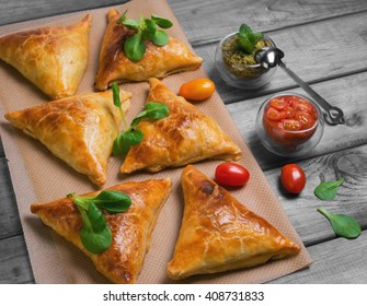 Delicious deep fried south Indian Samosa pies with meat, lettuce, mint chutney and tomato sauce on a gray wooden background in rustic style