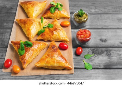 Delicious deep fried south Indian Samosa pies with meat, lettuce, mint chutney and tomato sauce on gray wooden background in rustic style, empty place for text, recipe