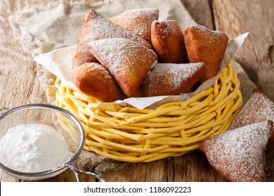 Delicious deep-fried donuts East African Mandazi with powdered sugar close-up in a basket on the table. horizontal