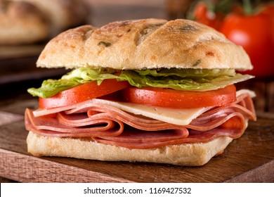 A delicious deli sandwich on cheddar jalapeno ciabatta bread with lettuce and tomato.