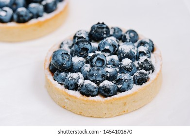 Delicious dessert blueberry mini tart with fresh berries and whipped cream. French cuisine. Berry pie with cream and icing sugar. Closeup. Shallow DOF