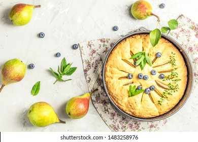 Delicious dessert blueberry tart with fresh berries and pears, sweet tasty cheesecake, berry pie on gray concrete surface table. French cuisine. Flat lay, top view, copy space for you text