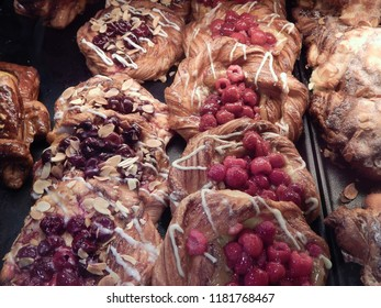 Delicious dessert buns with fresh raspberries on a tray in a cafe