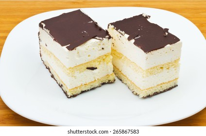 A delicious dessert on a white plate and wooden tray.