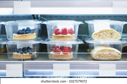 Delicious desserts with berries stored in plastic containers.Food store sell bakery product from refrigerator.Enjoy sweet baked food for lunch.cakes for coffee break.Tasty Italian snack foods
