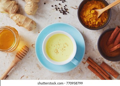 Delicious detox drink made of turmeric, ginger, milk, honey and cinnamon. Healthy and aromatic turmeric golden milk tea.