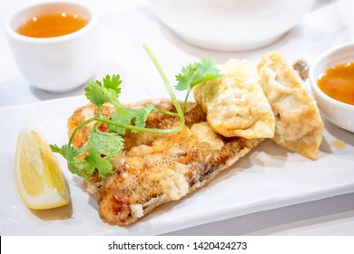 Delicious dim sum, famous cantonese food in asia - Fried fish and dumplings with lemon, sauce and tea in hong kong yumcha restaurant, close up