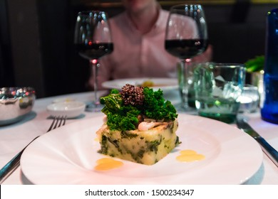 Delicious dinner in a 5-star hotel in Barcelona, Catalonia, Spain. Grilled mashed potatoes with kale and mushrooms. Gastronomic fusion food in this luxurious restaurant with red wine. March 2020.
