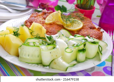 delicious dinner with fried pork chop,potato and fresh cucumber salad