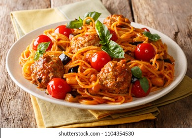 Delicious dinner: meat balls with pasta spaghetti, eggplant and tomatoes close-up on a plate on a table. horizontal