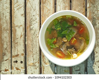 Delicious dish cooked with blessing meat for Muslims in Bangkok : Oxtail Soup with celery, tomato, cardamom seed and fried shallots in white bowl placed on wooden background. (top view/space for text)
