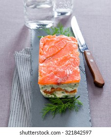 delicious dish with smoked salmon terrine with dill on gray granite gray board with a knife tablecloth close