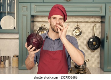 Delicious dish. Take old favorites and make delicious substitutions. Take favorite recipes and lighten them up. Man handsome chef holds violet cabbage thinking what delicious dish to cook.